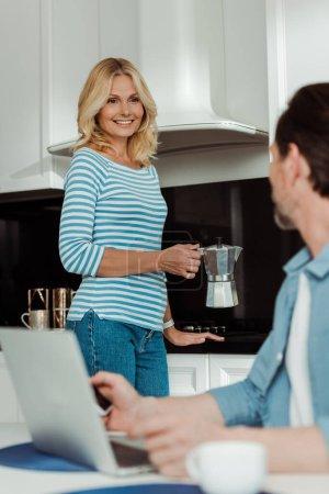 Selektiver Fokus der Frau, die eine Geysir-Kaffeemaschine in der Hand hält und ihren Mann mit Geräten in der Küche anlächelt