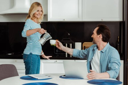 Selective focus of smiling woman pouring coffee near husband and laptop on kitchen table