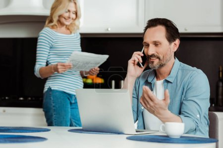 Photo for Selective focus of smiling man talking on smartphone near laptop while wife reading newspaper in kitchen - Royalty Free Image