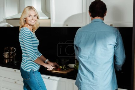 Mature woman smiling at camera while cutting vegetables near husband in kitchen