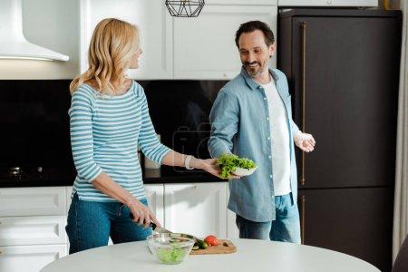 Foto de Hombre sonriente dando lechuga a esposa cortando verduras en la cocina - Imagen libre de derechos