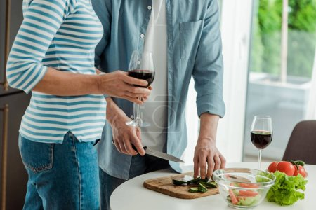 Cropped view of woman holding glass of wine near man cutting vegetables in kitchen