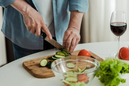 Photo for Cropped view of man cutting cucumber while cooking salad near glass of wine in kitchen - Royalty Free Image