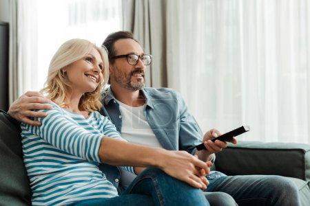 Photo pour Focus sélectif de l'homme tenant télécommande et embrassant femme souriante sur le canapé - image libre de droit