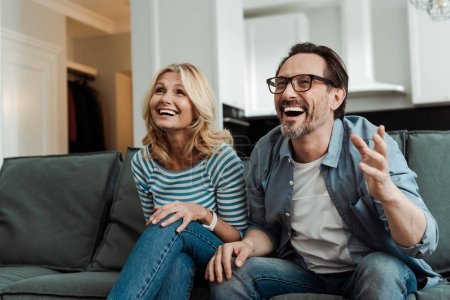 Mature couple laughing while sitting on couch