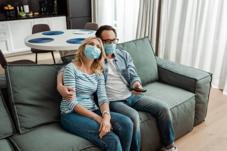 Photo for Mature man hugging wife in medical mask while watching movie on couch - Royalty Free Image