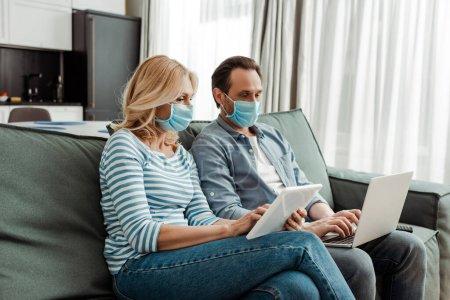 Photo pour Couple d'âge mûr dans des masques médicaux en utilisant un ordinateur portable et une tablette numérique sur le canapé - image libre de droit