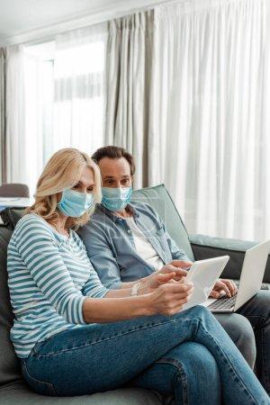 Photo pour Couple d'âge moyen dans des masques médicaux en utilisant une tablette numérique et un ordinateur portable dans le salon - image libre de droit