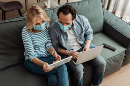 Photo for Overhead view of mature couple in medical masks using digital devices on couch - Royalty Free Image