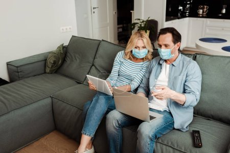 Photo for Man in medical mask pointing at laptop near wife with digital tablet on sofa - Royalty Free Image