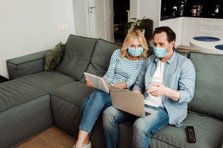 Photo pour Homme en masque médical pointant vers un ordinateur portable près de la femme avec tablette numérique sur le canapé - image libre de droit