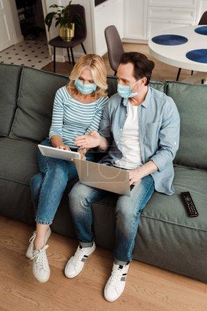 Photo pour Vue grand angle de l'homme dans le masque médical à l'aide d'un ordinateur portable et pointant avec la main près de la femme en utilisant une tablette numérique sur le canapé - image libre de droit