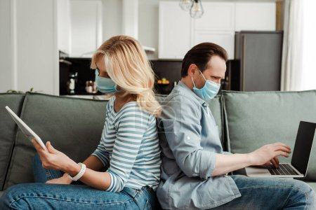 Photo for Side view of mature couple in medical masks using laptop and digital tablet on couch - Royalty Free Image