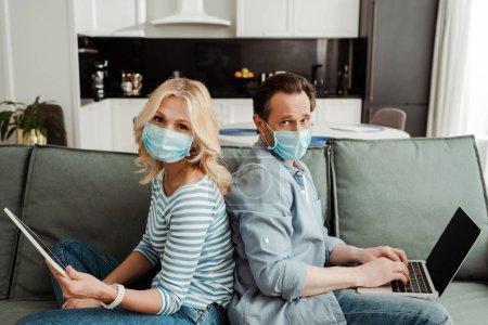 Photo pour Vue latérale du couple mature dans des masques médicaux regardant la caméra tout en utilisant des gadgets sur le canapé - image libre de droit
