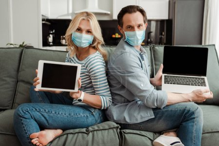 Photo for Side view of mature couple in medical masks showing laptop and digital tablet with blank screens on couch - Royalty Free Image