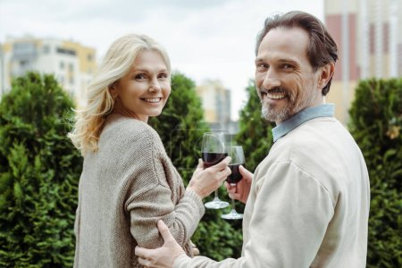 Photo for Side view of mature couple smiling at camera while holding glasses of wine on urban street - Royalty Free Image