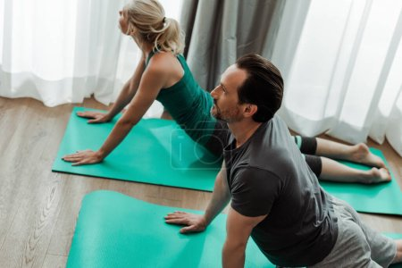 Photo for Selective focus of mature couple exercising on fitness mats at home - Royalty Free Image