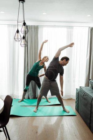Photo pour Homme mûr s'entraînant avec une femme souriante sur des tapis de fitness à la maison - image libre de droit