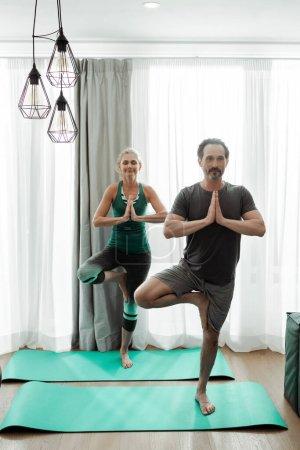 Photo pour Couple d'âge mûr pratiquant le yoga sur tapis de fitness à la maison - image libre de droit