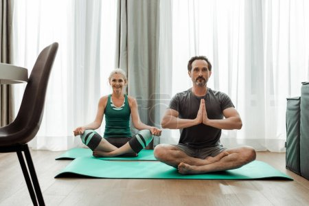 Photo pour Concentration sélective de l'homme mature pratiquant le yoga près de la femme souriante sur les tapis de fitness dans le salon - image libre de droit