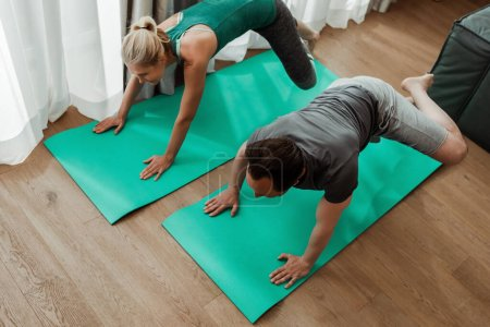 Overhead view of mature couple training on fitness mats together