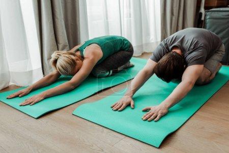 Photo pour Vue à angle bas du couple mature s'étirant sur des tapis de fitness à la maison - image libre de droit