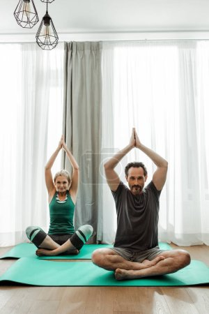 Photo for Mature couple practicing yoga on fitness mats in living room - Royalty Free Image