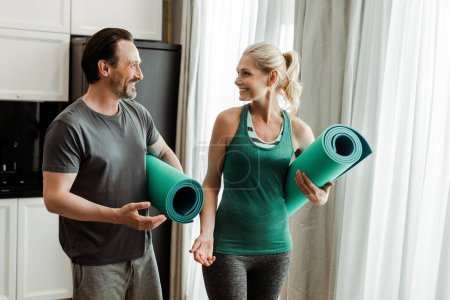 Smiling mature man pointing with hand on fitness mat near beautiful wife at home