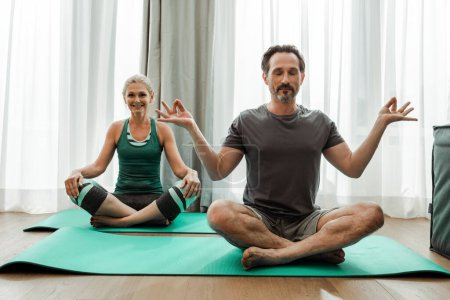 Photo for Mature man meditating on fitness mat near smiling wife in living room - Royalty Free Image