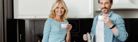 Panoramic crop of smiling mature couple drinking coffee in kitchen