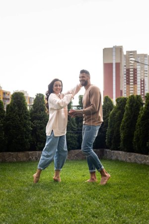 cheerful girl and bearded man standing on green grass outside