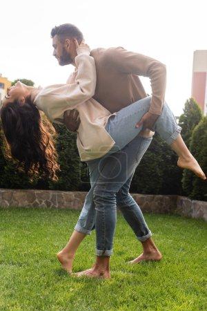 Photo pour Bel homme tenant jambe de copine attrayante tout en dansant sur l'herbe - image libre de droit