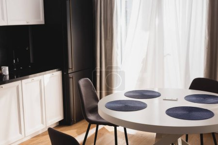 Photo for Smartphone on dining table near modern chairs - Royalty Free Image