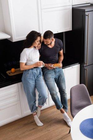 Photo pour Vue grand angle de fille heureuse tenant tasse et debout avec petit ami dans la cuisine - image libre de droit
