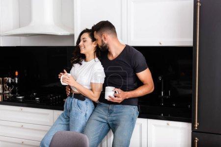 Photo pour Homme barbu et femme gaie tenant des tasses de café - image libre de droit