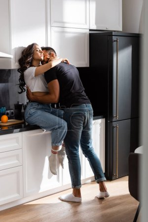 Photo for Bearded man kissing beautiful woman with closed eyes in kitchen - Royalty Free Image