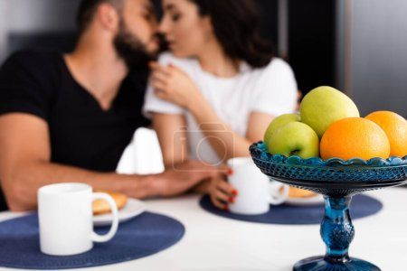 Photo for Selective focus of ripe fruits and cups near couple kissing in kitchen - Royalty Free Image