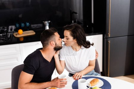 Photo for Young woman touching handsome boyfriend near cups on table - Royalty Free Image