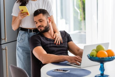 Photo for Selective focus of woman standing and touching bearded freelancer boyfriend near laptop while using smartphone - Royalty Free Image