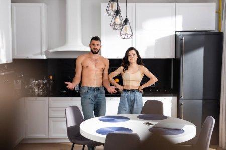 Photo pour Foyer sélectif de confus homme et fille avec les mains sur les hanches debout dans la cuisine moderne - image libre de droit