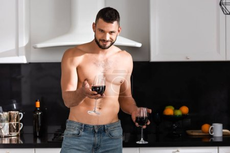 Photo for Happy and muscular man holding glasses with red wine - Royalty Free Image