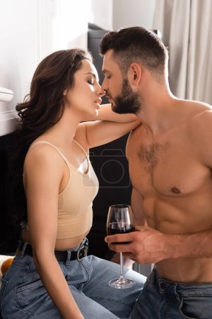 Photo for Side view of shirtless man holding glass of red wine near attractive girl with closed eyes - Royalty Free Image