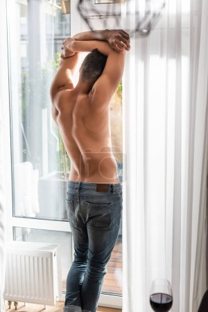 Photo for Selective focus of muscular man in jeans standing near window - Royalty Free Image