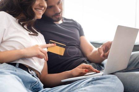 foyer sélectif de la femme heureuse tenant la carte de crédit près de copain barbu et ordinateur portable