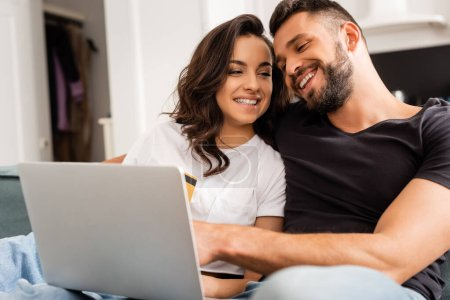 Photo for Happy woman holding credit card near bearded boyfriend and laptop - Royalty Free Image