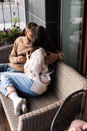 Foto de Pareja sentada en un sofá al aire libre y sosteniendo copas de vino mientras besan fuera. - Imagen libre de derechos