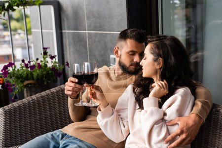handsome man hugging beautiful woman and clinking glasses of red wine outside