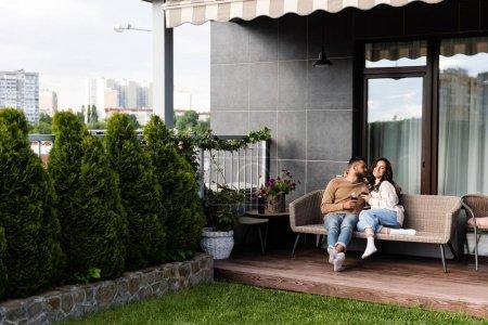 Foto de Un hombre guapo y una mujer feliz sentado en un sofá al aire libre y sosteniendo copas de vino. - Imagen libre de derechos