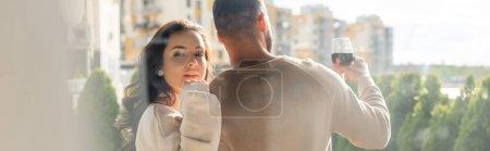 Photo pour Image horizontale de l'homme tenant verre de vin près de petite amie attrayante à l'extérieur - image libre de droit