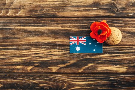 Photo pour Vue de dessus du drapeau australien près de fleur artificielle et biscuit sur la surface en bois - image libre de droit